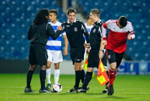 Referee Reuben Simon shakes hands with his assistants before kick-off