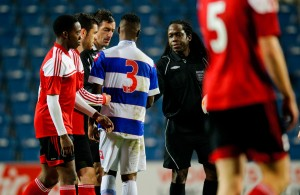 Referee Reuben Simon shakes hands with his assistants and players after the final whistle